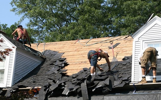 3 roofing workers stripping away old roofing materials