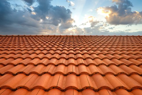 Looking up at brand new red roof tiles under a cloudy sky with sunlight breaking through the clouds