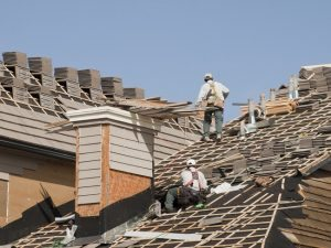 Roofers with tile stack on multi angle roof