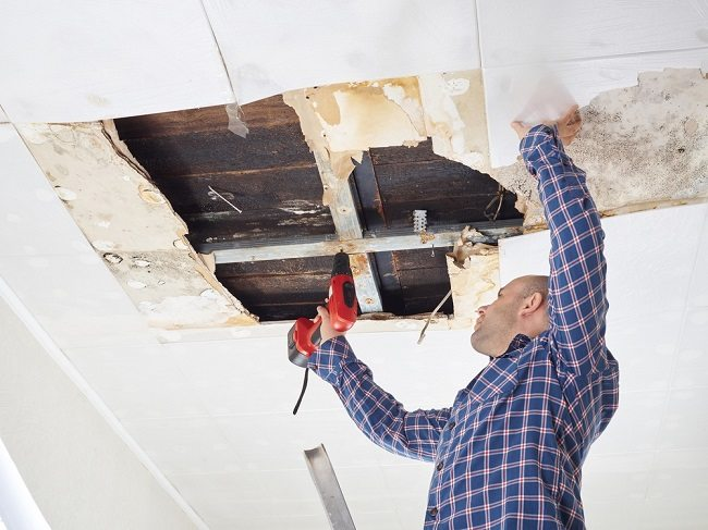 A handyman drilling into the roof through the ceiling