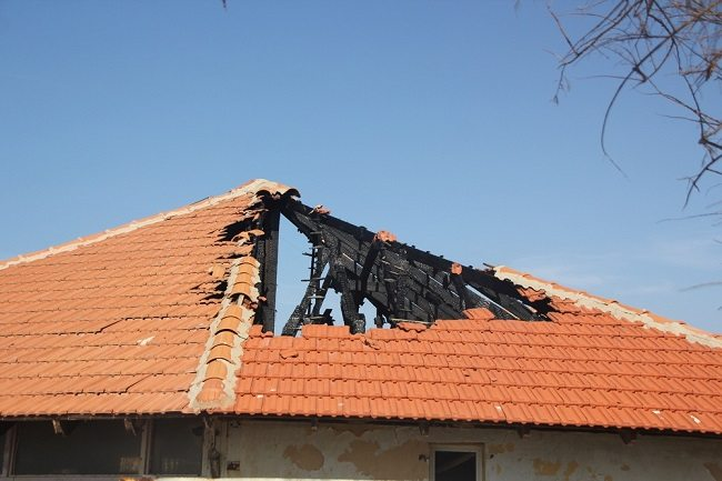 Picture of damaged roof with large area of tiles missing