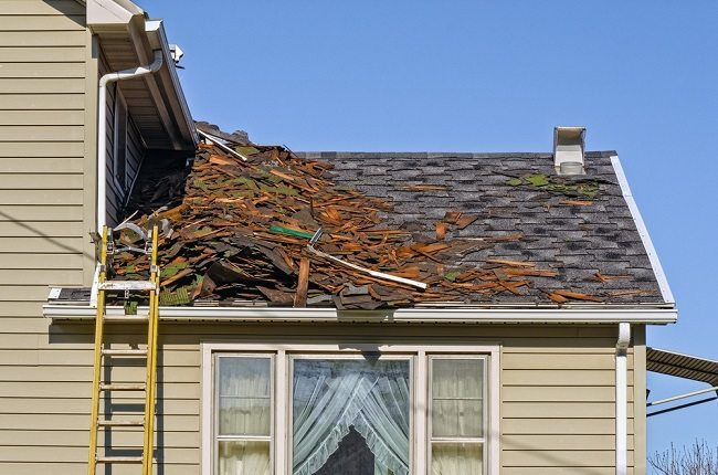 Roof with debris and dislocated grey tiles