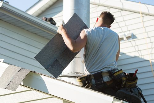 Man with tool belt working on a roof