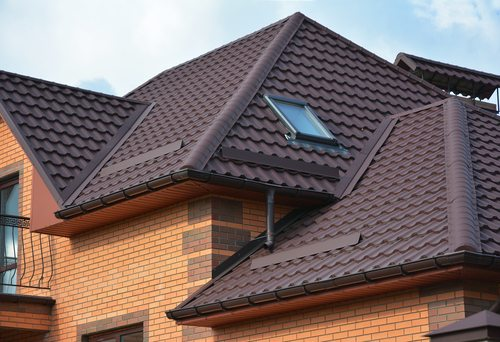 Beautiful new brown roof tiles on brand new home with three separate angled roofs