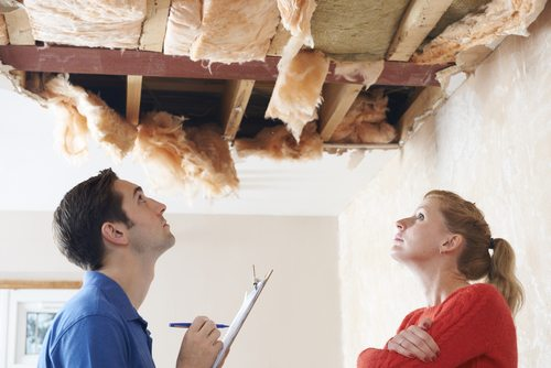 Male roofer and female householder looking at large, unsightly hole in ceiling