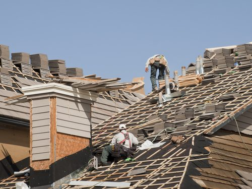 Two men working on multiple roofs, placing tiles on support frames