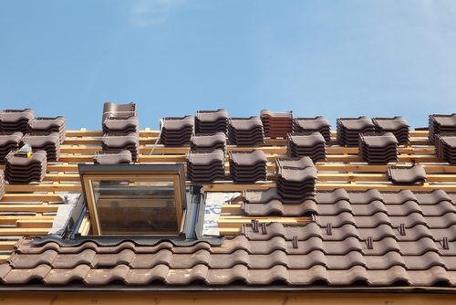 Stacks of brown roof tiles on roof in process of construction