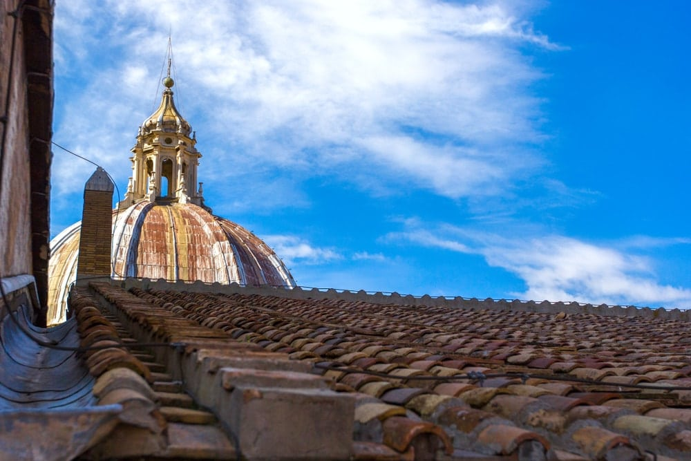 View at the dome of Saint Peter's Basilica and tiled roof in Vatican City, Rome, Italy