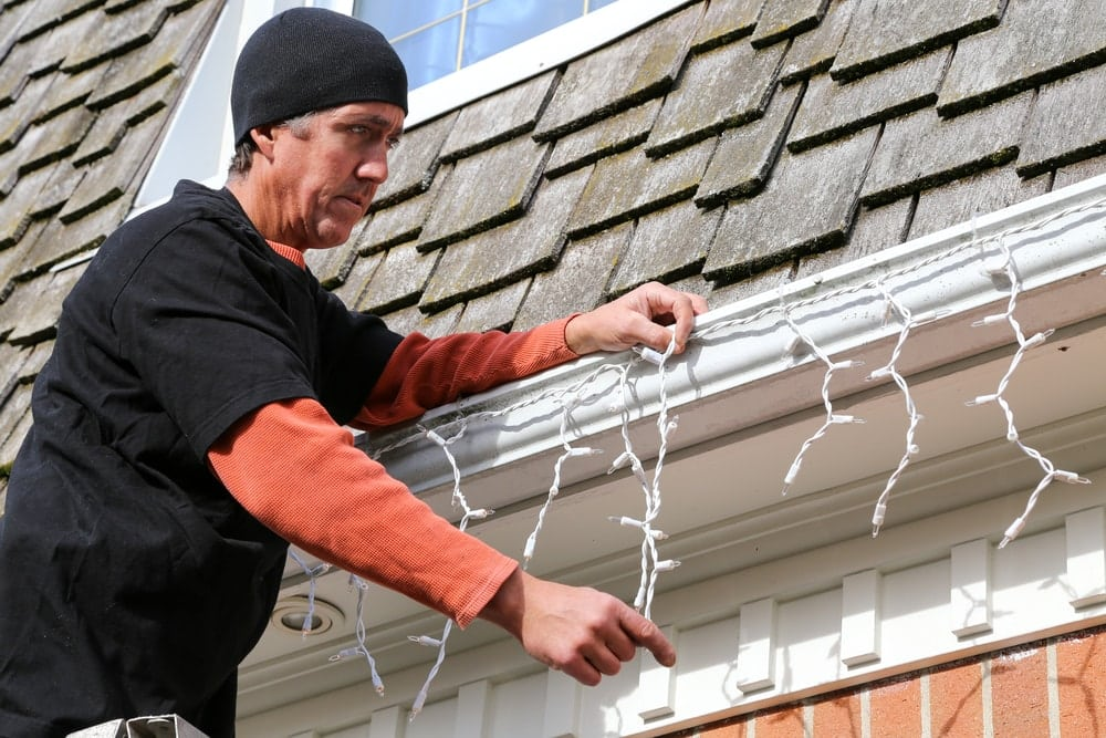 a man at the top of a ladder adjusting the strands of exterior Christmas lights he is hanging on his house